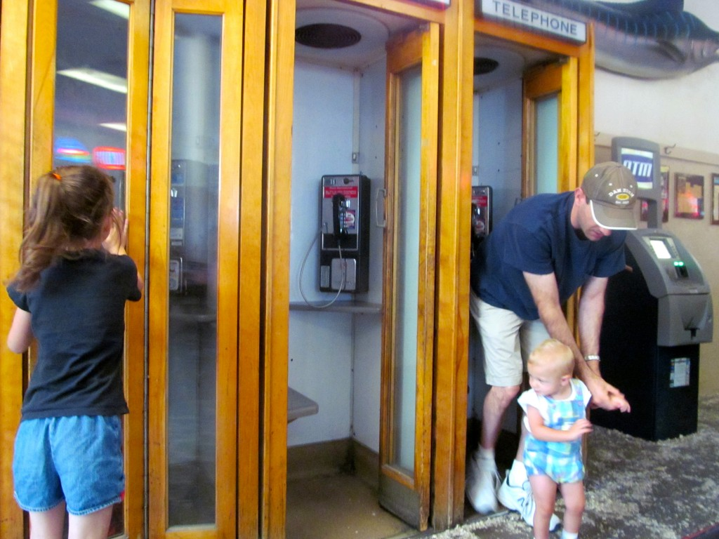 Kids playing in the line of historic phone booths.